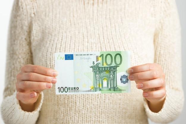 Eine frau hält hundert euro in den händen. finanzielles und kommerzielles konzept.