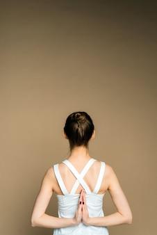 Eine frau hält ihre hände hinter dem rücken und praktiziert yoga auf beigem hintergrund. ein schönes junges mädchen meditiert in der pose von parshvottanasana