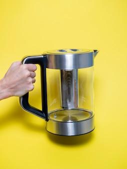 Eine frau hält in der hand einen silberfarbenen wasserkocher aus metall mit verschiedenen wasserheizmodi auf leuchtend gelbem hintergrund.