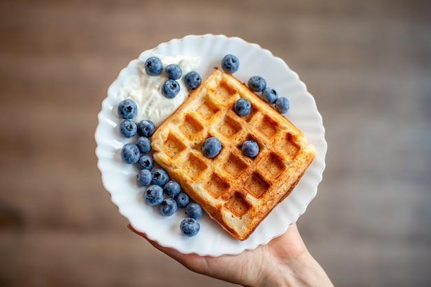 Eine frau hält in der hand einen teller, auf dem frische waffeln mit beeren bereitstehen. hausgemachte waffeln mit erdbeeren und blaubeeren. leckeres frühstück mit beeren.