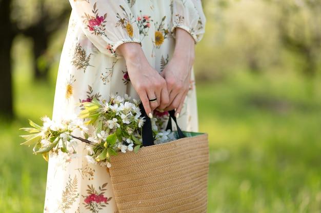 Eine frau hält in ihren händen eine stilvolle weidentasche mit blühenden blumen im grünen park. frühlingsromantische stimmung und naturschönheit