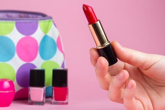 Eine frau hält roten lippenstift in den händen. damenaccessoires, kosmetik