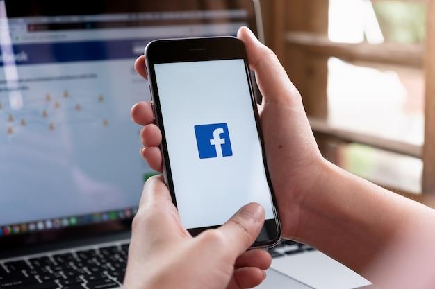 Eine frau hält smartphone mit facebook in der anwendung auf dem bildschirm