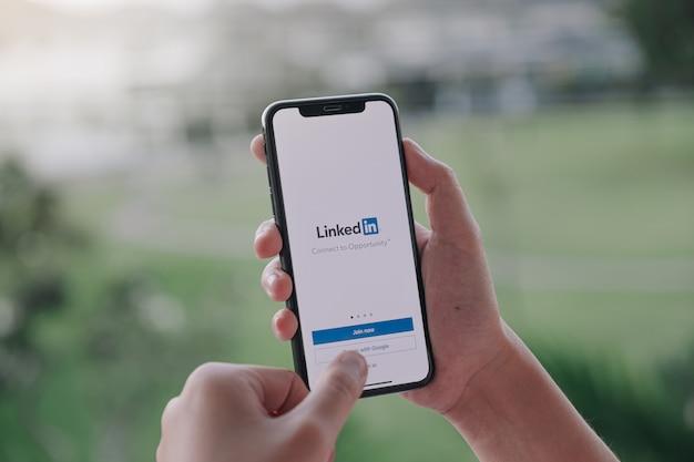Eine frau hält smartphone mit linkedin-anwendung auf dem bildschirm