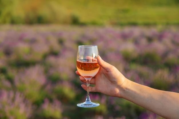 Eine frau hält wein in gläsern. picknick im lavendelfeld. selektiver fokus. natur.
