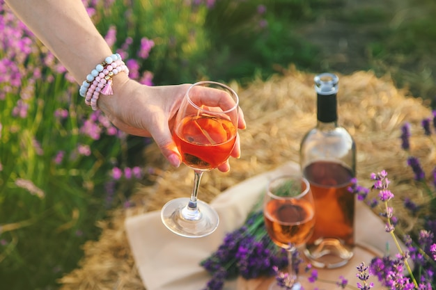 Eine frau hält wein in gläsern. picknick im lavendelfeld. selektiver fokus.