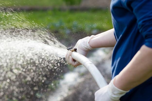 Eine frau hände mit schlauch, der ihren riesigen garten während der schönen frühlings- / sommerzeit gießt; harte arbeit; senior; gartenarbeit