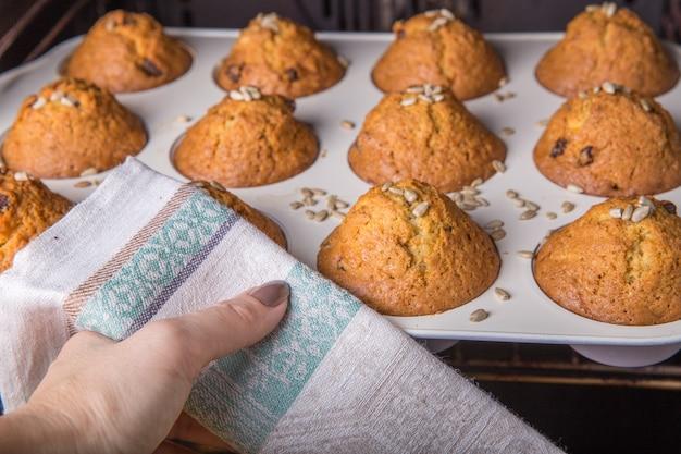 Eine frau holt weihnachts-cupcakes aus einem heißen ofen