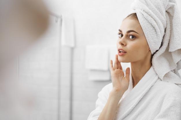 Eine frau im bademantel im bademantel vor einem spiegel schaut auf ihr gesicht