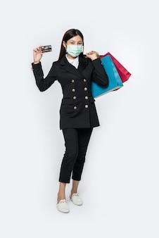 Eine frau im dunkeln und mit maske geht einkaufen, trägt kreditkarten und viele taschen