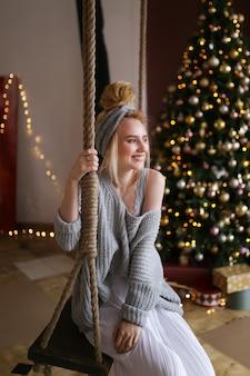 Eine frau im gemütlichen schlafanzug entspannt sich und ruht sich zu hause am baum und am kamin aus
