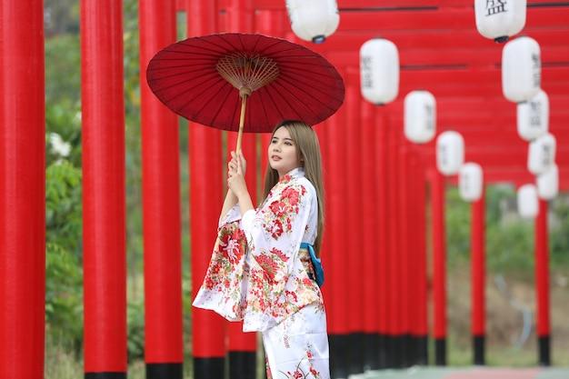 Eine frau im kimono, die regenschirm hält, der am schrein im japanischen garten hereinkommt.