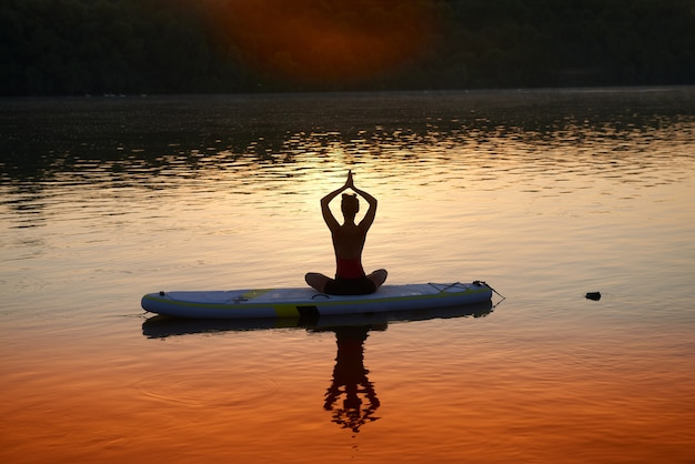 Eine frau im lotussitz sitzt auf einem padelbrett und meditiert mit sonnenuntergang im hintergrund