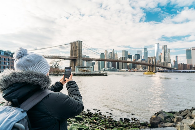 Eine frau im mantel fotografiert mit ihrem handy nach new york city - nahaufnahme