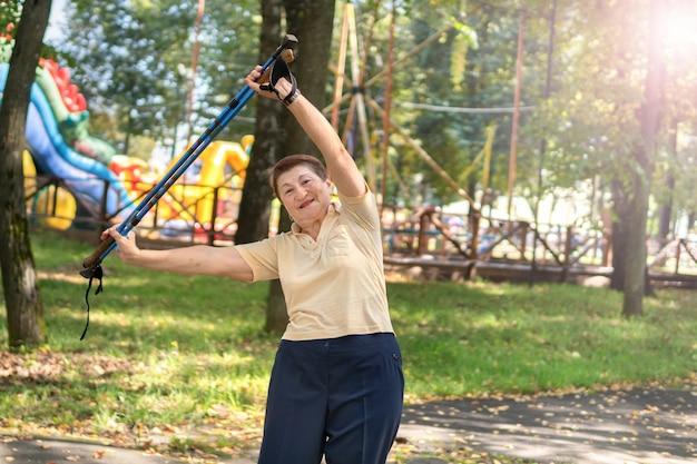 Eine frau im park geht an einem sonnigen sommertag mit stöcken nordisch. ältere frau mit guter laune beschäftigt sich mit dem morgendlichen training.