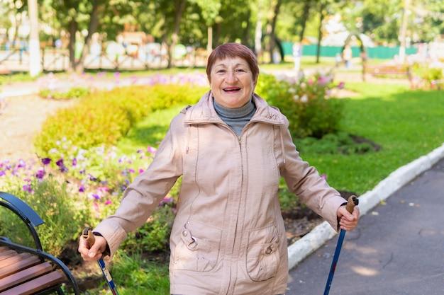 Eine frau im park geht an einem sonnigen sommertag mit stöcken spazieren
