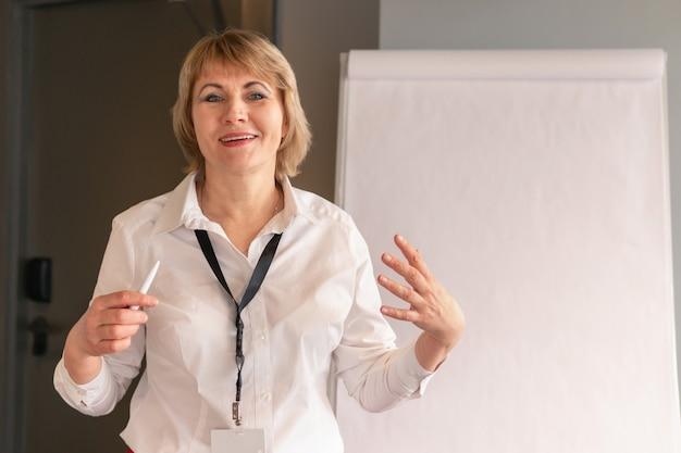 Eine frau im weißen hemd trainiert zuhörer im geschäftsraum
