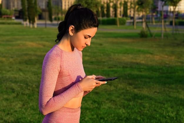 Eine frau im yoga-anzug macht es am frühen morgen mit einem telefon in der hand im morgengrauen.