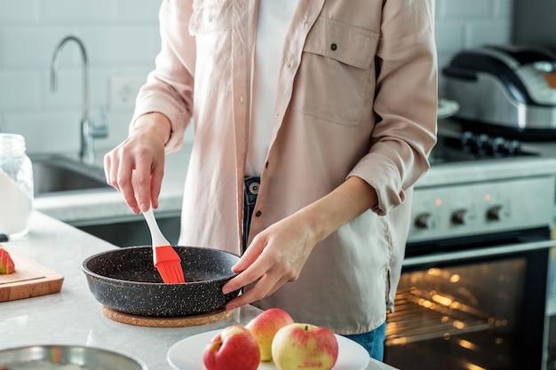 Eine frau in der küche fettet eine auflaufform mit butter ein, um einen kuchen zu backen. kochen.