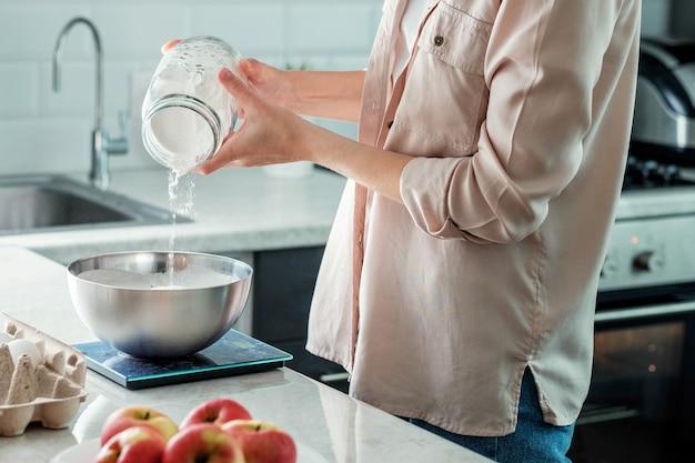 Eine frau in der küche gibt reismehl in eine schüssel, um apfelkuchen zu backen. kochen