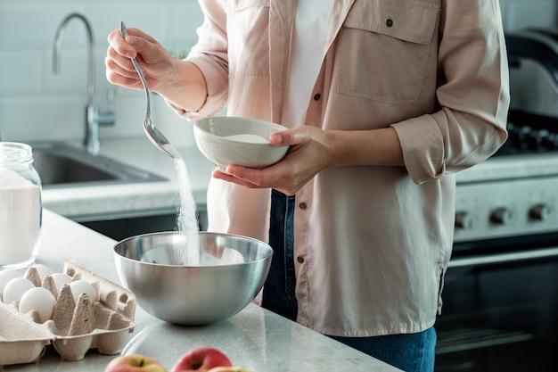 Eine frau in der küche gießt kristallzucker aus einer schüssel. kochen.