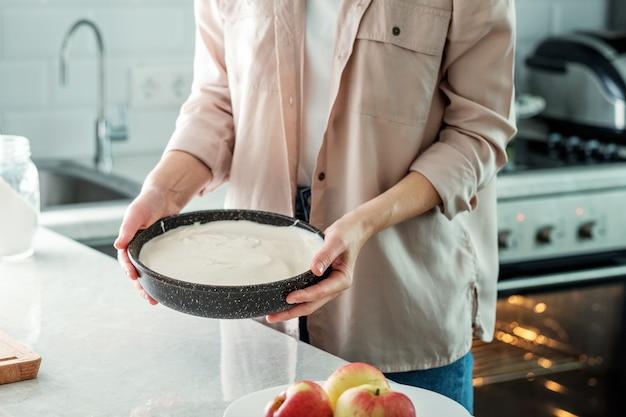 Eine frau in der küche hält eine auflaufform mit einem teig für einen kuchen mit äpfeln. essen zubereiten. backen aus reismehl