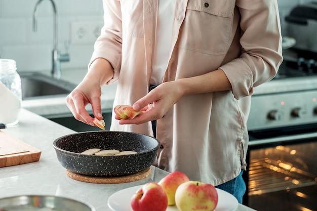 Eine frau in der küche legt einen frischen, in scheiben geschnittenen apfel in einer auflaufform aus. kochen. backen aus reismehl