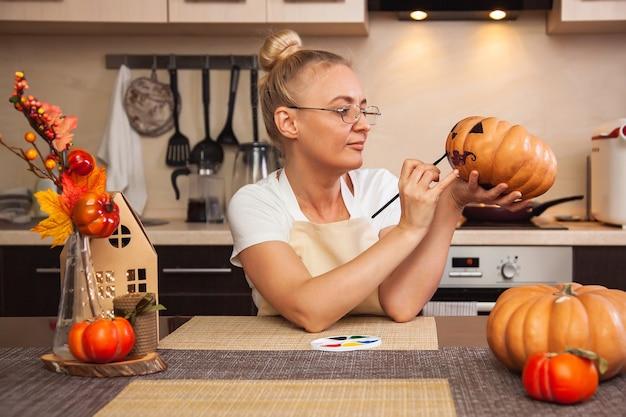 Eine frau in der küche malt einen kürbis für halloween in einem raum mit herbstdekor und einem lampenhaus. gemütliches zuhause und vorbereitung auf halloween.