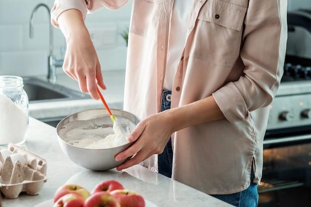 Eine frau in der küche mischt zutaten in einer schüssel mit einem spatel, um einen kuchen mit äpfeln zuzubereiten. kochen