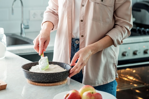 Eine frau in der küche nivelliert den teig für einen apfelkuchen mit einem spatel in einer auflaufform. kochen. backen aus reismehl