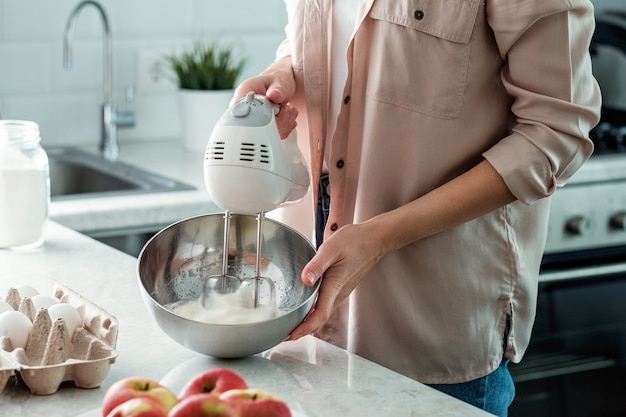 Eine frau in der küche peitscht hühnerweiß mit zucker mit einem mixer zu einem apfelkuchen. kochen.