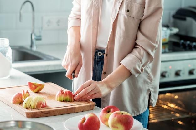 Eine frau in der küche schneidet frische äpfel, um einen kuchen zu backen.