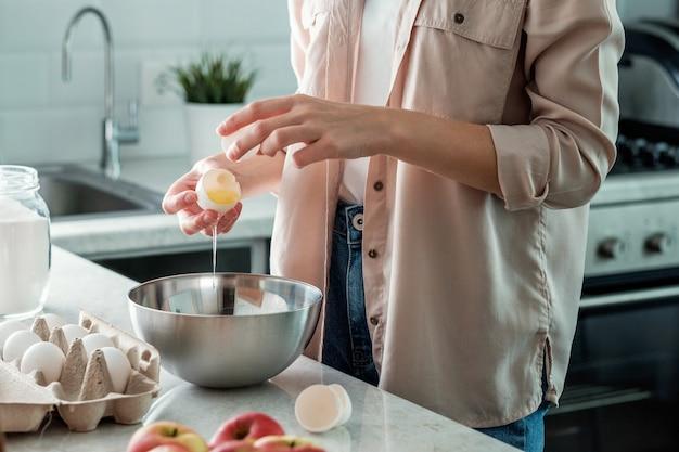 Eine frau in der küche zerbricht ein hühnerei mit einer schüssel. kochen.