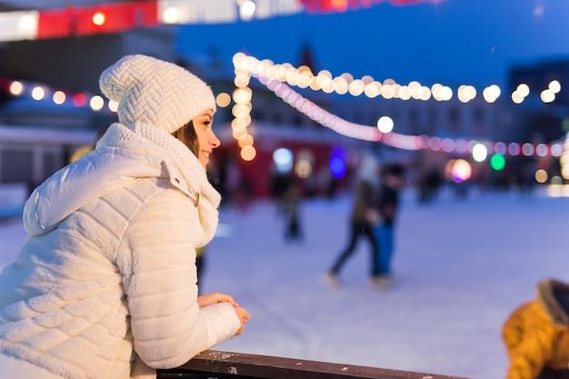 Eine frau in der nähe der eisbahn schlittschuhlaufen silvester und weihnachtslichterkette eis- und schneestimmungskonzept