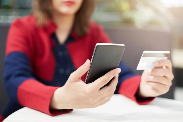 Eine frau in der roten kleidung, die handy in händen hält, die mit kreditkarte online bezahlen
