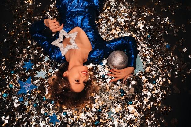 Eine frau in einem blauen kleid mit pailletten lächelt und liegt unter einem fallenden bunten konfetti auf dem boden.