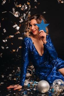 Eine frau in einem blauen paillettenkleid lächelt sitzend auf dem boden mit konfetti auf einem schwarzen hintergrund.