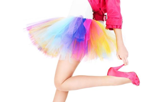 Eine frau in einem bunten ballerinakleid und rosa absätzen posiert auf weißem hintergrund