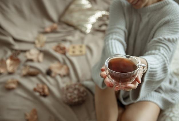 Eine frau in einem gemütlichen strickpullover hält eine tasse tee in den händen, kopierraum.