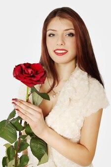 Eine frau in einem goldenen anhänger in form eines herzens mit der rose