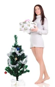 Eine frau in einem grauen kleid posiert in der nähe eines weihnachtsbaumes mit einem geschenk in den händen und schaut weg