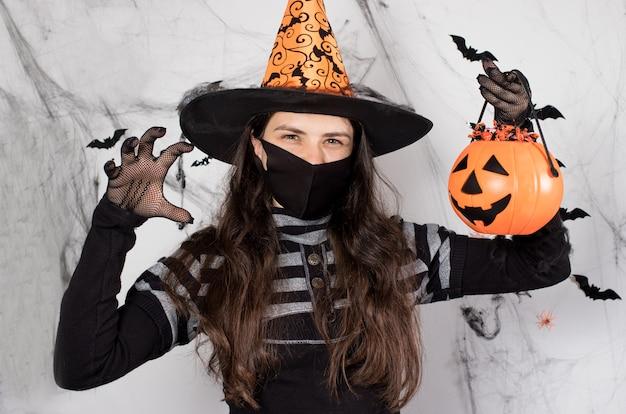 Eine frau in einem hexenkostüm in einer schutzmaske hält einen eimer kürbis mit süßigkeiten.