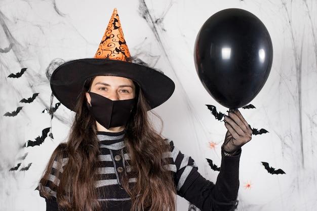 Eine frau in einem hexenkostüm in einer schwarzen medizinischen maske hält einen ballon.