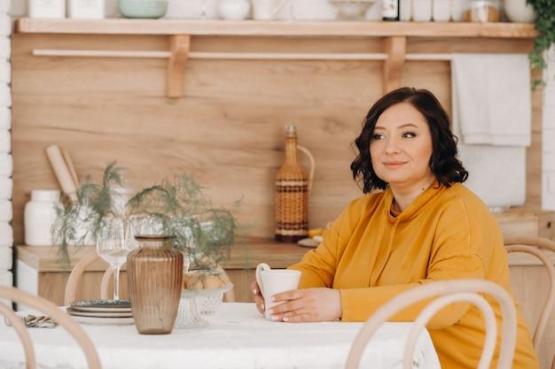 Eine frau in einem orangefarbenen hoodie sitzt an einem tisch in der küche und trinkt kaffee.