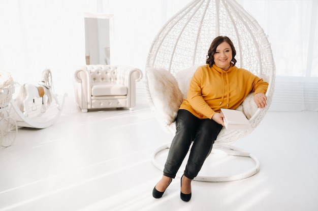Eine frau in einem orangefarbenen hoodie sitzt auf einem ungewöhnlichen stuhl mit einem buch in den händen.