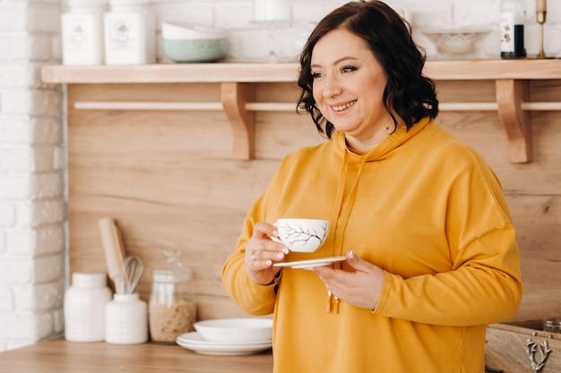Eine frau in einem orangefarbenen sweatshirt trinkt kaffee in der küche zu hause.