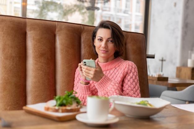 Eine frau in einem restaurant in einem warmen pullover schaut sich etwas am telefon an, ein köstliches gesundes frühstück und matcha latte auf dem tisch