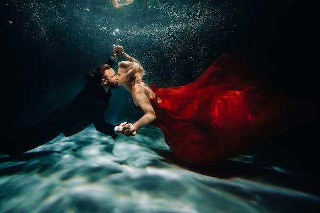 Eine frau in einem roten kleid und ein mann in einem anzug küssen sich unter wasser. ein paar schwimmt unter wasser.