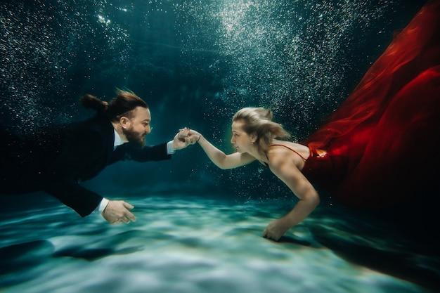 Eine frau in einem roten kleid und ein mann in einem anzug treffen sich unter wasser. ein paar liebende unter wasser