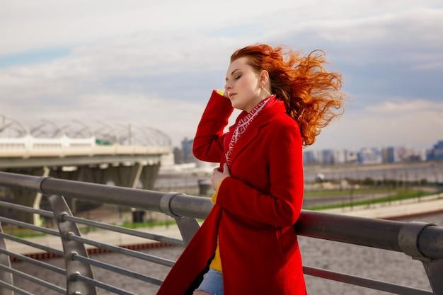 Eine frau in einem roten mantel steht auf der brücke und glättet ihre haare im wind.